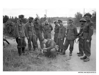 Troops of the 1st Rifle Brigade search German prisoners near Tilly-sur-Seulles on 13 June 1944.
