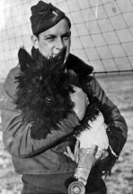 First Lt. Walter J. Konantz, a pilot of the 55th Fighter Group, holds his Scottie dog, Lassie II, who is nursing a leg injury (as is evinced by a plaster cast).