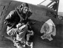 "First Lt. Quince L. Brown of the 84th Fighter Squadron and Bristow, Oklahoma, reputed as the ""first man in the European theater to destroy four German planes on one day while flying a Republic P-47 Thunderbolt fighter,"" poses with his dog, a German shepherd pup. Quince was shot down and captured — and subsequently murdered by German civilians on 6 September 1944. His dog was sent on to his folks in Oklahoma. (Roger Freeman Collection FRE309)"