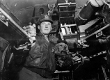 """First Lt. Robert C. Peterson, a navigator of the 44th Bomb Group, sits inside his B-24 Liberator with the crew's mascot: """"Pilot Officer Rusty."""" Rusty allegedly took part in several missions. (Associated Press)"""
