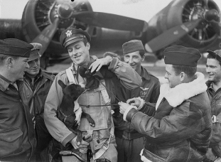 """The crew of a 390th Bomb Group B-17 commanded by 2nd Lt. Robert W. Biesecker of Lexington, North Carolina pets their mascots """"Scrappy"""" the dog and """"Joe"""" the monkey. Scrappy was adopted by the crew during training in the United States while Joe was adopted at an airbase in England. (Roger Freeman Collection FRE1593)"""