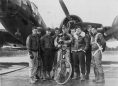 """2nd Lt. Robert W. Biesecker of the 390th Bomb Group poses with his crew and their pets, """"Scrappy"""" the dog and """"Joe"""" the monkey, in front their B-17 """"Honey Chile"""" (#42-31027) in October 1943. (Roger Freeman Collection FRE1593)"""