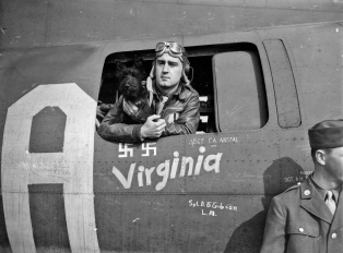 "Captain James A. Verinis of the 91st Bomb Group poses with his Scottie, ""Stuka,"" in the waist gun position of his B-17 Flying Fortress ""Memphis Belle"" on 30 June 1943, following the conclusion of his crew's tour of duty. Verinis was the co-pilot of the ""Memphis Belle."" (Roger Freeman Collection FRE3500)"