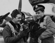 Two airmen of the 96th Bomb Group place an oxygen mask on their dog in front of a B-17G Flying Fortress. (Roger Freeman Collection FRE3962)