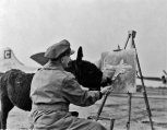 "War artist Frank Beresford is assisted by ""Lady Moe,"" the donkey mascot of the 96th Bomb Group. (Roger Freeman Collection FRE3968)"