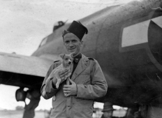 "Lt. Albert C. Rood of the 390th Bomb Group poses with his new terrier, ""Eager,"" in England, after returning from an arduous shuttle mission to Regensburg and North Africa in August 1943. (Roger Freeman Collection FRE3968)"