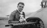 Staff Sergeant Antoni Bednarchuk of the 303rd Bomb Group, a former bus driver from Providence, Rhode Island, poses with his dog in April 1943. (Roger Freeman Collection FRE4189)