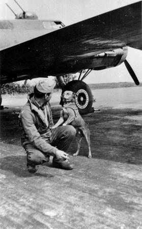 An airman of the 306th Bomb Group with his dog, underneath the wing of a B-17 Flying Fortress. (Roger Freeman Collection FRE4397)