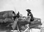 "A bomber crewman of the 381st Bomb Group lifts up his dog, ""Meatball"" on 10 March 1944. (Roger Freeman Collection FRE4835)"