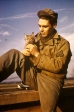 "William ""Bill"" Pulliam, a photographic officer of the 91st Bomb Group, pets his cat, ""Cross Eyes"" at Bassingbourn. (Roger Freeman Collection FRE5671)"