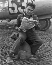 A gunner in the 451st Bomb Group sits with his dog before a mission. (Roger Freeman Collection FRE8795)