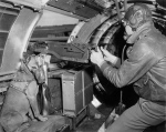 """Sgt. Harold Rogers of the 401st Bomb Group with his dog mascot """"Mister,"""" in the waist gun position of a B-17 Flying Fortress nicknamed """"Un Petit Peu."""" """"Mister"""" allegedly flew several missions with his master who designed a custom respirator for him. (Roger Freeman Collection FRE9719)"""