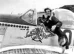 "Fighter ace, Lt. Ralph K. ""The Kid"" Hofer of Salem, Missouri and the 4th Fighter Group, plays with his Alsatian, ""Duke."" When Hofer was killed in a dogfight over Berlin in July 1944, Duke was adopted by fellow pilot, Lt. ""Deacon"" Hively, and taken home after the war."
