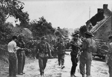 German officers and troops surrender to Canadian forces at St. Lambert-sur-Dives in August 1944. At the left of the picture, with pistol in hand, is an officer identified as Major David Currie, his face begrimed by three days of battle during which his command had destroyed seven enemy tanks, twelve 88mm guns, and 40 vehicles, while killing 300 German troops, wounding 500 and capturing 2,100 — a feat which won him Victoria Cross, the Empire's greatest award for battlefield gallantry.