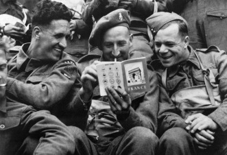 British troops take a light-hearted look at a brochure on France issued by their unit shortly before the invasion. (AFP)