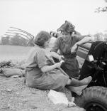 A British gunner of a 25-pounder battery talks to a French farm girl on 20 July 1944.