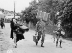 Private First Class Clayton C. Hayes of Fox Company, 505th Infantry Regiment helps Normandy residents, Madame Digeon and Jacques Birette, with their luggage along the Route de Chef-du-Pont on the outskirts of St-Mère-Église on June 8, 1944. Hayes would die in combat in Holland on September 20, 1944, during Operation Market Garden. (NARA 111-SC-190287)