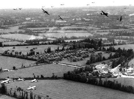 "American C-47 Dakotas swirl over a typical stretch of Norman countryside, over the Cotentin Peninsula, with hedgerows and trees bordering fields, after cutting loose their CG-4A gliders over Landing Zone W, between Les Forges and Sébeville/Les Fontaines. The French N13 highway runs through the center of the image while the town of St-Mère-Église is two miles away (to the left in the photograph). The aircraft were participating in Operation ""Elmira,"" the reinforcement of the US 82nd Airborne Division on the evening of June 6, 1944. (AP)"