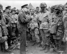 "General Dwight D. Eisenhower speaks to a group of American paratroopers from Easy Company, 502nd Parachute Infantry Regiment, at the 101st Airborne Division's camp in Greenham Common, England, on the evening of June 5, 1944, moments before the men boarded aircraft to participate in the airborne assault of the continent. Eisenhower's message was to the point: ""Full victory — nothing else."" Among the men in the image are Sgt. Fred Lindsey (holding a sketchbook, behind and to the left of Eisenhower's back), Sgt. Russell Wilmarth (behind Eisenhower's chin), Lt. Wallace C. Strobel (wearing a ""23"" tag). Ralph ""Bud"" Thomas (on Strobel's left), Corporal Donald Kruger (wearing musette bag, in front row, far right). (Library of Congress; US Army photograph SC 194399)"