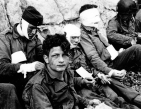 "Wounded members of the 3rd Battalion, 16th Infantry Regiment receive cigarettes and food in a sheltered stretch of beach at the 6th Naval Beach Battalion's medical aid station at the foot of chalk cliffs in the ""Fox Red"" sector of ""Omaha"" beach on the morning of D-Day. The soldier looking at the camera is identified as Private Nicholas A. Fina, 22-years old, of 'I' Company and New York state. (NARA 111-SC-189910)"