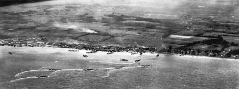 "An aerial photograph of the ""Sword"" beach sector showing Hermanville and with le Breche located in the right third of the picture, near the patch of white on a field. The middle part of the picture, where landing craft are clustered, shows the ""Queen Red"" beachfront."