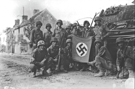 Americans of all creeds and colors come together to hold up a captured Nazi flag at Chambois, France, on 20 August 1944, a day before the collapse of German troops in the Falaise Pocket. Contrary to popular belief that the American segregation of the 1940s normalized racism to banal levels, an examination of narratives and memoires of the era shows that there actually existed a level of cordiality, if not mutual respect, among the various American peoples. That is not to say, however, that African Americans were not regarded as second-class citizens as a matter of official policy. (Corbis)
