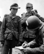 "A captured Georgian from the German 795th Ost Battalion gives his name to a US Army captain at ""Utah"" Beach. At the time, American troops believed the man was a Japanese soldier in German uniform. In the years after the war he was identified as a ""Yang Kyoungjong,"" a Korean national inducted into the Russian Red Army, who was in turn captured by the German Army in 1942. The theory went on speculate that ""Kyoungjong"" immigrated to the United States after the war, where he died in the 1990s. The man's facial features, however, reveal him to be a member of the ethnic minorities of Georgia. (US Office of Public and International Affairs)"